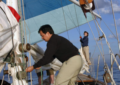 Crew Member Denis Fong works the spinnaker halyard as we set the chute during the 2005 Newport to Ensenada race.